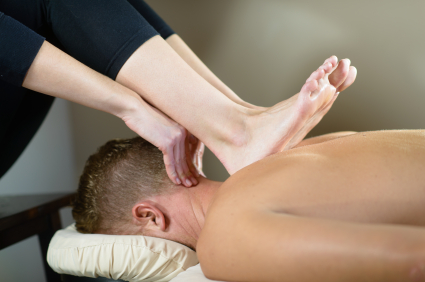 Shoulder pain/tension: Therapist uses heals and feet to press shoulders away from ears and massage the upper back.